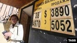Женщина смотрит на табло с выросшим курсом доллара и евро в пункте обмена валюты. Москва, 16 сентября 2014 года.