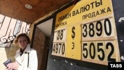 Ақша айырбастау орнында доллар мен еуро бағамы көрсетілген жазу жанында тұрған әйел. Мәскеу, 16 қыркүйек 2014 жыл.