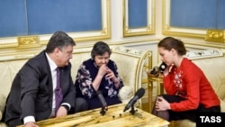 Президент Украины Петр Порошенко, мать и сестра Надежды Савченко разговаривают с украинской военнослужащей по телефону. Киев, 19 апреля 2016 года.