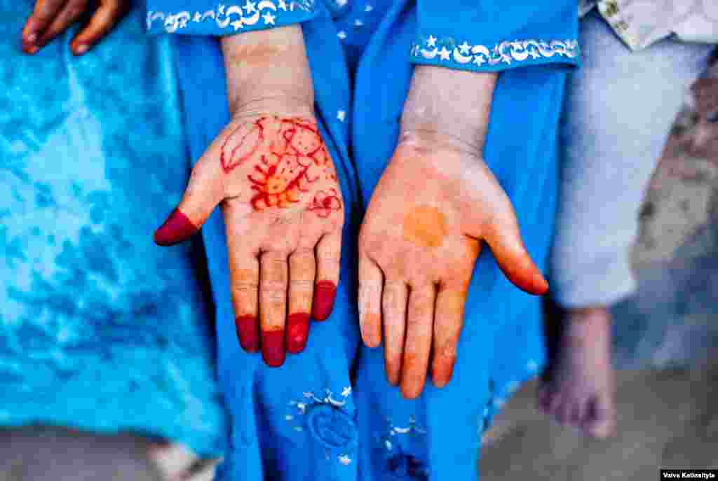 A refugee woman shows henna decorations on her hands.