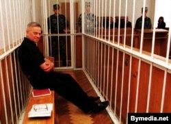 Былы міністар сельскай гаспадаркі Васіль Лявонаў за кратамі ў клетцы ў залі суду