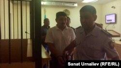 Житель Уральска Нургали Байкатов, обвиняемый по делу о крупной контрабанде сайгачьих рогов, в сопровождении судебного конвоя. 23 июня 2017 года.