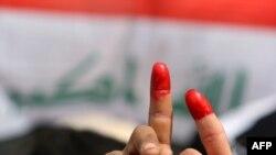 متظاهرون عراقيون يرفعون سباباتهم الملونة بالأحمر في تظاهرة ساحة التحرير