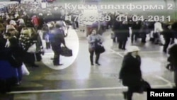 A screenshot from video surveillance cameras in the Minsk subway of a suspect (top left) carrying a bulky sports bag on April 11.