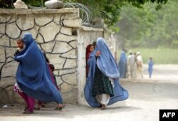 Women scurry for cover as during a international military patrol in eastern Afghanistan.