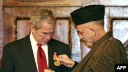 Afghan President Karzai (right) presents President Bush with a medal in Kabul.