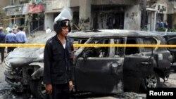 Өртенген көлік қаңқасының қасында тұрған полиция өкілі. Каир, 29 маусым 2015 жыл.