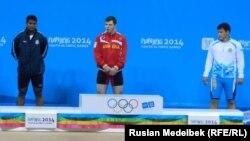 Казахстанский тяжелоатлет Жаслан Калиев (справа) на награждении по итогам соревнования на юношеских Олимпийских играх в Нанкине. 21 авугста 2014 года.