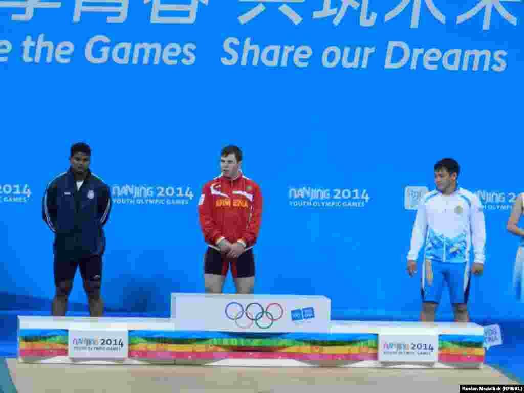 Қазақстандық ауыр атлет Жасұлан Қалиев (оң жақта) 77 килограмм салмақта жасөспірімдер олимпиадасының қола жүлдесіне ие болды. Ол қоссайыс бойынша 310 килограмм (жұлқа көтеруде - 139 кг, серпе көтеруде - 171 кг) салмақ көтерді. Нанкин, Қытай, 21 тамыз 2014 жыл.