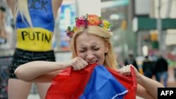 U.S. - Inna Shevchenko rips a Russian flag as she joins topless activists of the Ukrainian protest group Femen demonstrates against Russian intervention in Ukraine and in support of US sanctions on March 6, 2014 in New York's Times Square.