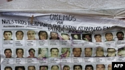 A banner with the pictures of the 33 miners trapped in the San Esteban gold and copper mine in Copiapo