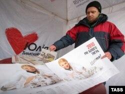 Распространитель предвыборных листовок и плакатов Юлии Тимошенко перед выборами президента Украины. Киев, 30 января 2010 года.