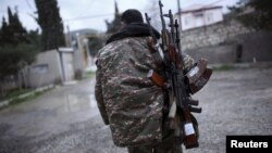 Armenia - A soldier of the self-defense army of Nagorno-Karabakh carries weapons in Martakert province, which according to Armenian media was affected by clashes over the breakaway Nagorno-Karabakh region, April 4, 2016