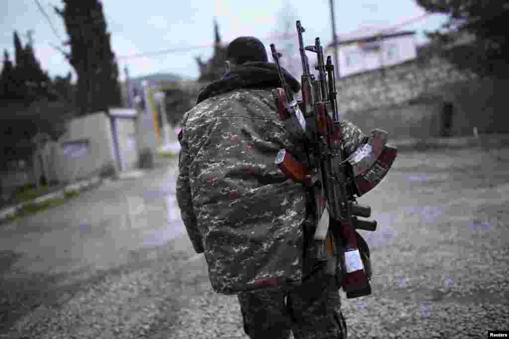 A soldier from the self-defense army of Nagorno-Karabakh carries weapons in Martakert province, which was reportedly affected by clashes over the breakaway region. (Reuters/Vahan Stepanyan)