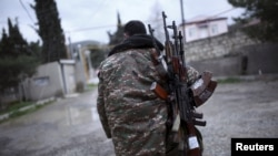 A soldier with separatist forces in Nagorno-Karabakh carries weapons in Martakert province, which was reportedly affected by recent clashes over the breakaway Caucasus region.