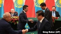 Президент Казахстана Нурсултан Назарбаев (слева на заднем плане) и президент Китая Си Цзиньпин наблюдают за церемонией подписания межправительственных соглашений. Пекин, 7 июня 2018 года.