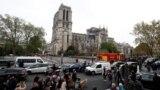 Notre Dame baş ybadathanasynda dörän ýangyn söndürilenden soňra adamlar ony synlaýarlar we surata düşürýärler.