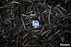 A passport photo left behind by a migrant is seen among seaweed on a beach on the Greek island of Lesbos.