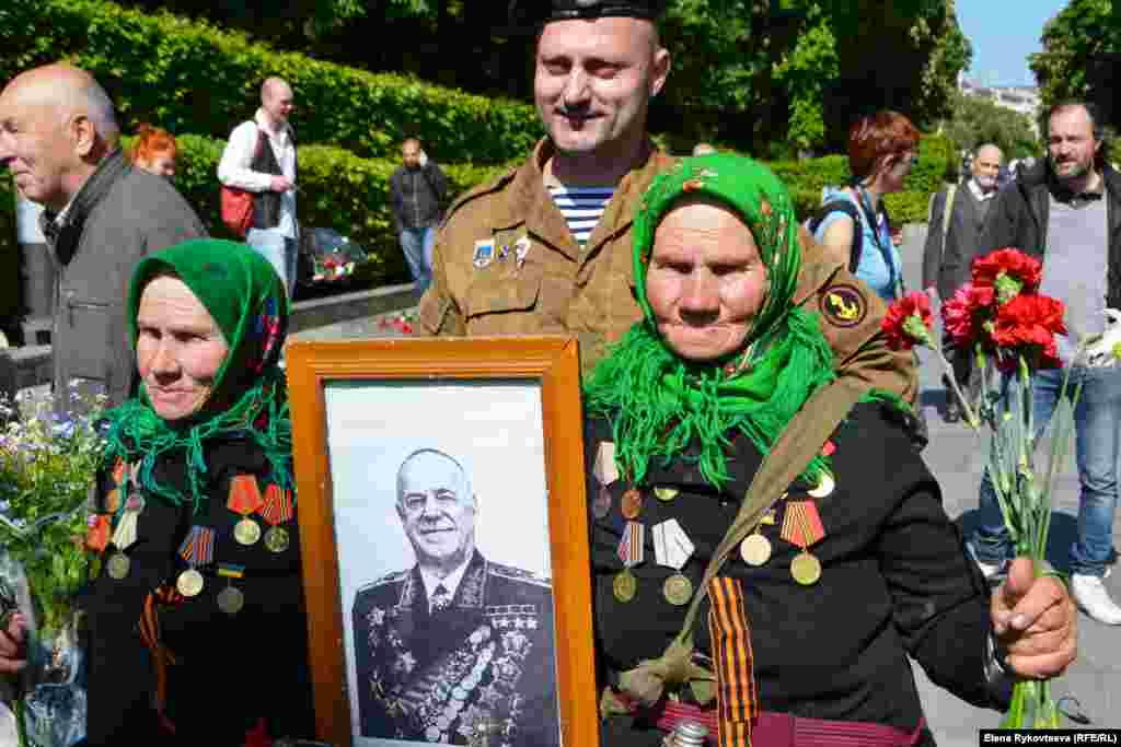 Two women in Kyiv, Ukraine, hold a portrait of former Red Army commander and World War II hero Georgy Zhukov, the most decorated officer in Soviet history.