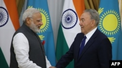 Президент Казахстана Нурсултан Назарбаев (справа) пожимает руку премьер-министру Индии Нарендре Моди, прибывшему в Астану для участия в саммите ШОС. 8 июня 2017 года.