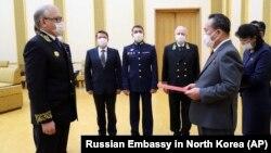Посол России в Северной Корее Александр Мацегора (слева) передает северокорейскому чиновнику медаль, которая вручена Ким Чен Ыну. 5 мая 2020 года.