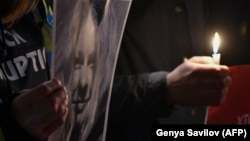 People hold a picture of Kateryna Handzyuk in front of the Interior Ministry in Kyiv in remembrance of the anticorruption campaigner on November 4.