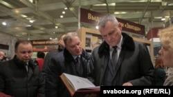Ігар Шуневіч на выставе разглядае факсымільнае выданьне Бібліі Скарыны