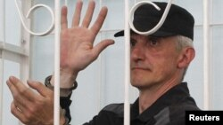 Platon Lebedev gestures inside the defendants' box during a 2011 court hearing.