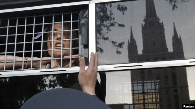 An opposition activist looks out from a police bus after being detained near a protest camp on May 17.