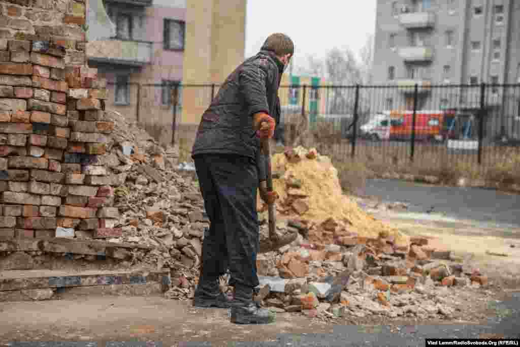 Несмотря на звук взрывов со стороны поселка Опытное, коммунальщики убирают листья с улиц. Этот местный житель убирает остатки битого кирпича.