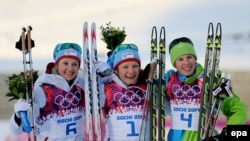 Norway's Maiken Caspersen Falla (center) celebrates winning the gold medal next to silver medalist Ingvild Flugstad Oestberg (left) of Norway and bronze medalist Vesna Fabjan (right) of Slovenia after the women's cross-country freestyle sprint race on February 11.