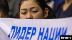 Студентка Академии спорта и туризма держит плакат на собрании в поддержку инициативы проведения досрочных выборов президента. Алматы, 20 февраля 2015 года.