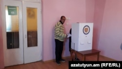 A person helping an elderly woman to vote in Armenian local elections last year.
