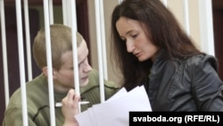 Mikita Likhavid, speaks with advocate in a guarded cage during a court hearing in Minsk in March.