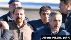 باتیستی (چپ) در ۱۴ ژانویه امسال، در زمان استرداد از بولیوی توسط پلیس ایتالیا همراهی میشود.