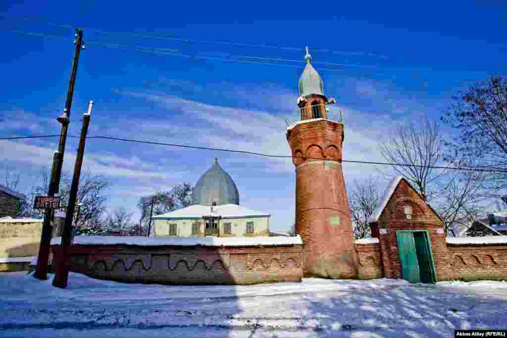 A brick minaret stands in front of the wood-framed mosque in the village of Nugedi, in Azerbaijan's Guba region.