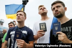 People holding their Ukrainian passports at a rally in central Kyiv to support Mikheil Saakashvili, who was stripped of his Ukrainian citizenship.