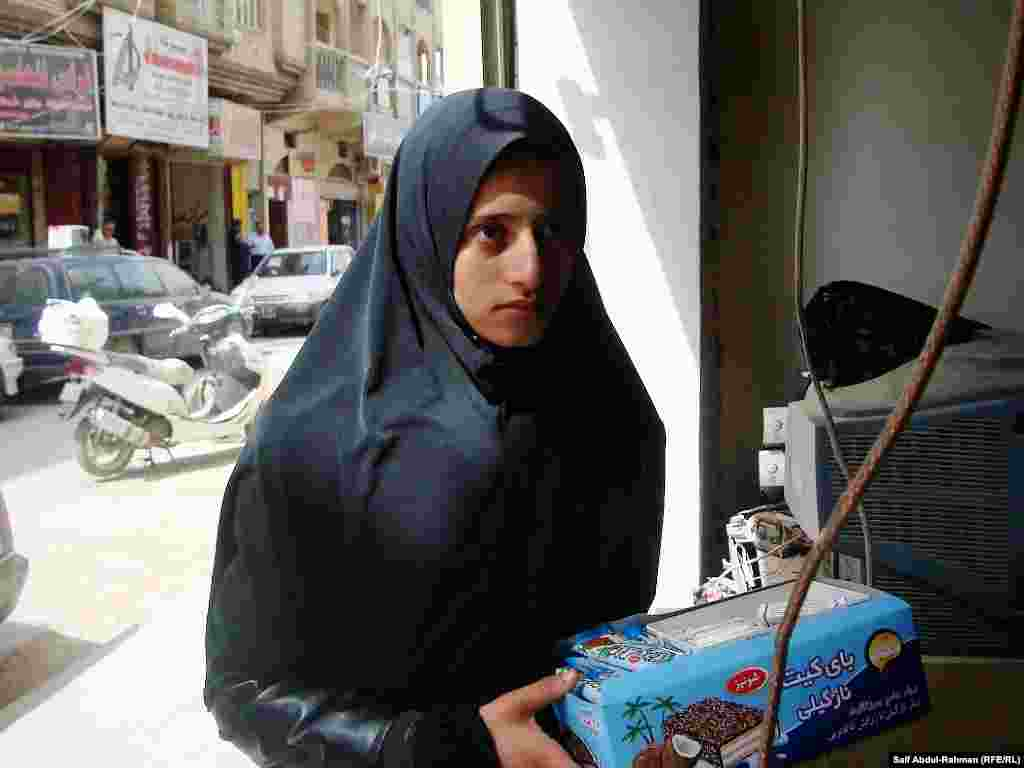 An adolescent girl sells sweets in the Iraqi city of Kut.