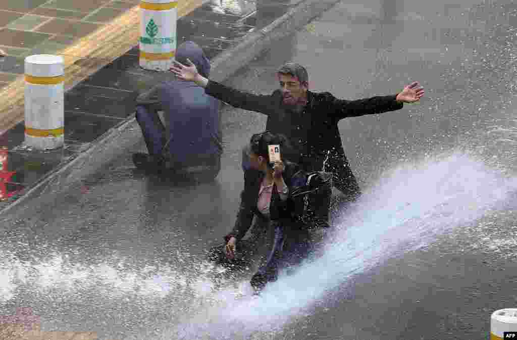 A Turkish woman shows her identity card next to another protestor as riot police use water cannon during clashes after hundreds of people tried to reach Ankara's main Kizilay Square to celebrate May Day in Ankara. (AFP/Adem Altan)