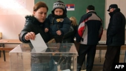 A Kosovo Serb woman with her child casts her ballot at a poling station in Kosovska Mitrovica on February 15.