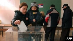 A Kosovar Serb woman with her child casts her ballot at a polling station in Kosovska Mitrovica.