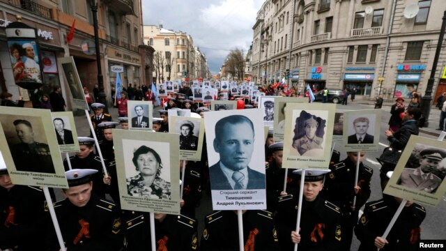 Russian cadets whose relatives fought in World War II carry their portraits during a parade in St. Petersburg on May 5.