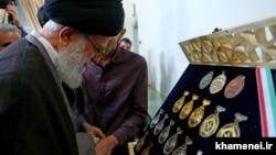 رهبر جمهوری اسلامی در حال نظاره مدالهای برندگان المپیادهای جهانی و کشوری پس از دیداری با برندگان در مرداد ۹۵