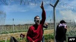 Мігранти біля діри в паркані, зведеному на македонсько-грецькому кордоні, 10 квітня 2016 року