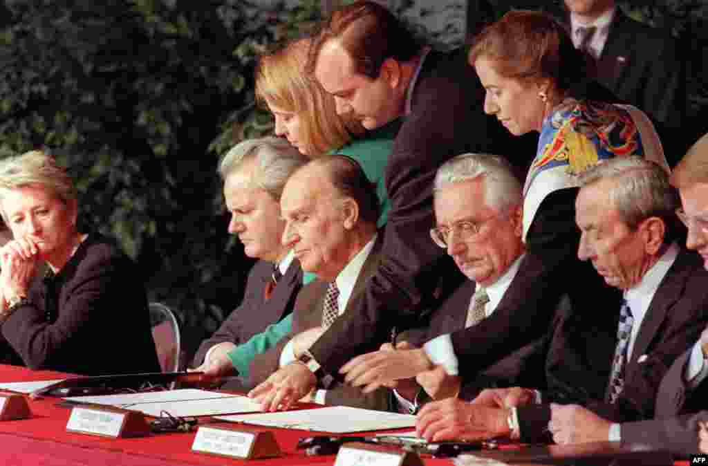 Leaders sign their initials on the draft of the Dayton peace agreement on November 21, 1995, at the conclusion of the Proximity Peace Talks at the Wright Patterson Air Force Base near Dayton, Ohio. Serbian President Slobodan Milosevic is sitting second from the left. To his left are Bosnian President Alija Izetbegovic, Croatian President Franjo Tudjman and U.S. Secretary of State Warren Christopher.