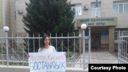 Гражданский активист Динара Мубарак возле здания суда держит плакат с призывом к освобождению бывшего президента компании «Казатомпром» Мухтара Джакишева. Семей, 9 августа 2019 года.