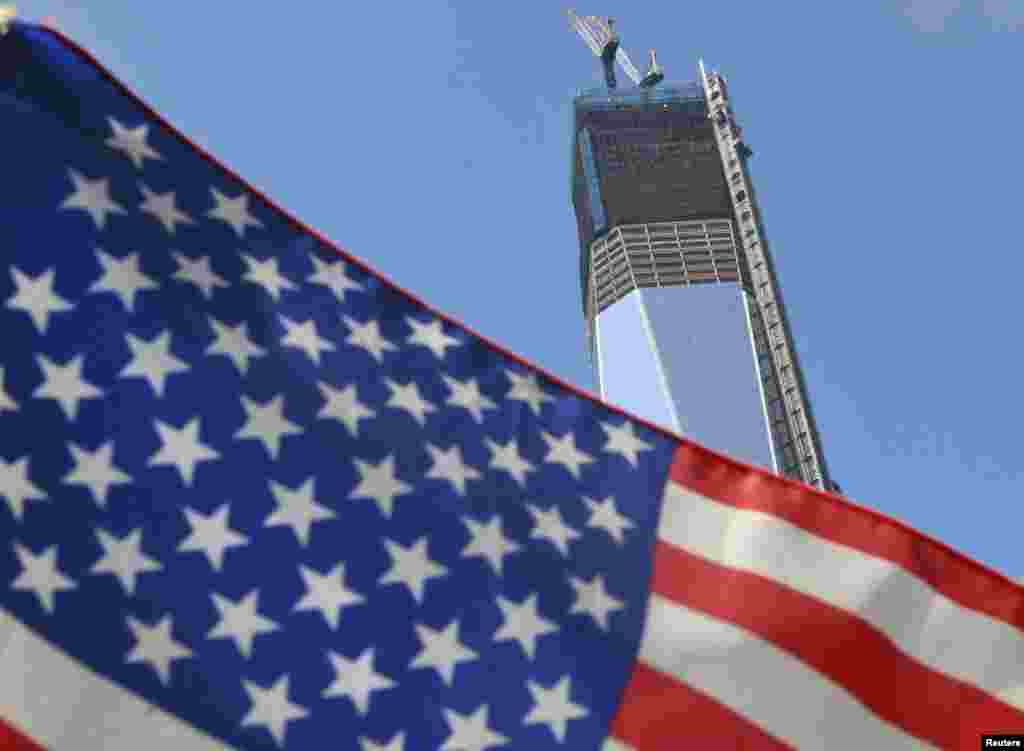 The unfinished One World Trade Center, the flagship of the redeveloped site, is seen behind a U.S. flag on September 7, 2012. The tower, due to be completed in 2014, will rise to 1,776 feet.