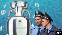 Ukrainian police officers pass a placard depicting the Euro 2012 trophy on Independence Square in Kyiv.
