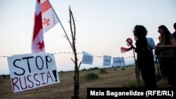 Грузини з плакатом «Stop Russia» протестують проти російської окупації Південної Осетії, село Хурвалеті на фактичному кордоні Грузії, липень 2015 року
