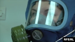 A nurse demonstrates a protective suit at a Moscow infectious-diseases clinic.